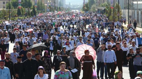 """Local residents walk to attend a mass protest in Chechnya's provincial capital Grozny, Russia, Monday, Sept. 4, 2017. Tens of thousands of people have taken to the streets in Russia's predominantly Muslim Chechnya to protest what the Chechen leader called """"genocide of Muslims"""" in Myanmar. (AP Photo/Musa Sadulayev)"""