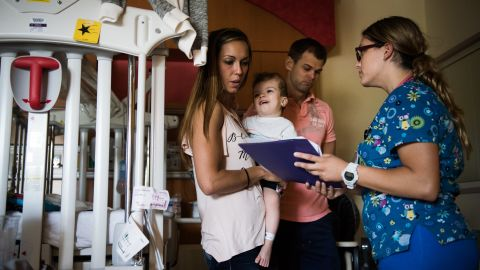 Nicole McDonald holds Jadon while looking over discharge information on September 1, as they prepare to leave the rehab facility and head home as a family for the first time.