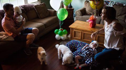 Christian McDonald holds his son Anias as Nicole McDonald checks on Jadon at home with the family dogs, Taz and Tyson.