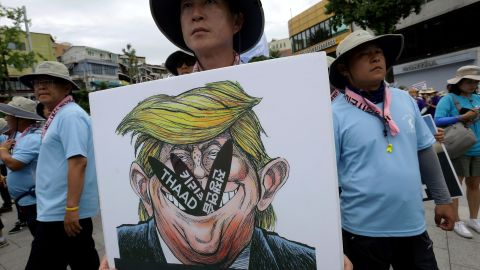 A protester holds a placard with an illustration of US President Donald Trump during a rally against THAAD near the US army base on August 14, 2017 in Seoul, South Korea.