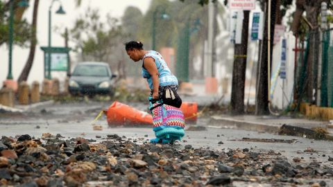 A woman makes her way through debris in Fajardo, Puerto Rico, on September 7.