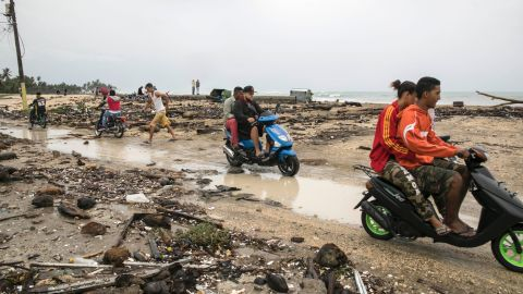 Nagua residents ride through an area affected by the storm on September 7.
