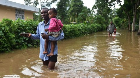 A man carries a child through a flooded street in Fort-Liberte, Haiti, on Friday, September 8.