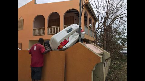 A man looks at a vehicle turned upside down in the British territory of Anguilla.