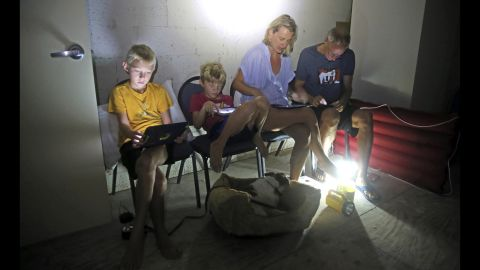 Members of the Blinckman family use their personal devices in a stairwell utility closet as Hurricane Irma went over Key West, Florida, on September 10.