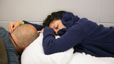 Yaya Lopez holds her fiance, Howard Lopez, while they sleep in a middle-school hallway in St. Petersburg on September 10.