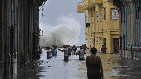People wade through a flooded street as a wave crashes in Havana on Sunday, September 10.