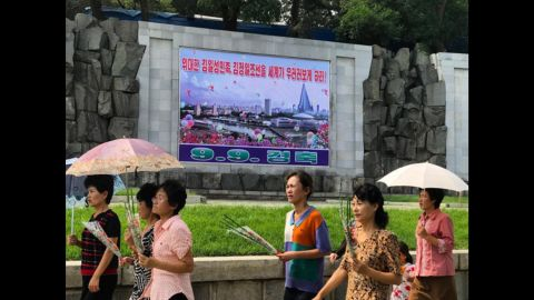"""Pyongyang residents walk past a poster marking the 69th DPRK Foundation Day on September 9. It reads """"Let the entire world look up to the great Kim Il Sung nation and Kim Jong Il Korea."""""""