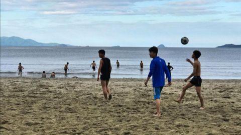 North Korean high school students play on a beach at Wonsan, on September 11, 2017.