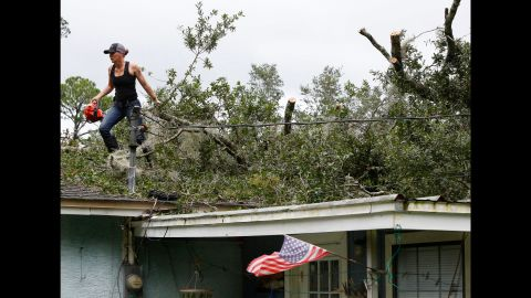 Ashley Tomberg drags a tree branch from the roof of a neighbor's house in Gainesville, Florida, on September 11.
