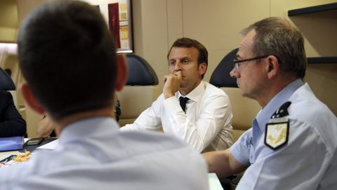 France's President Emmanuel Macron (2ndR) confers with officials aboard the presidential plane en route to Guadeloupe Island, the first step of his visit to French Caribbean islands, on September 12, 2017.