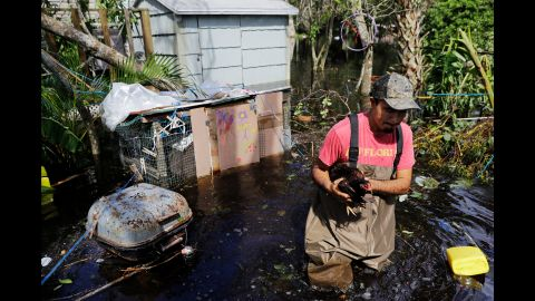 Jose Encarnacion pulls a chicken from a cage as he gathers belongings from his flooded house in Bonita Springs, Florida, on September 12.