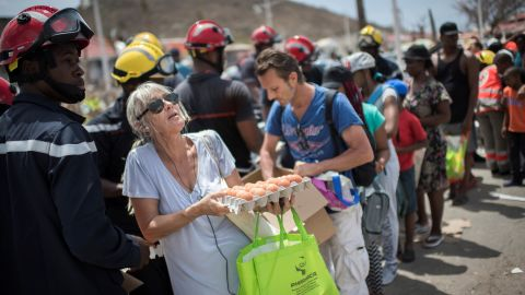 People collect food that was delivered by emergency workers in the Sandy Ground area of Marigot, St. Martin, on Tuesday, September 12.