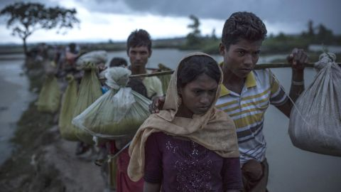 Rohingya refugees walk across paddy fields on September 9, after crossing the border in Gundum, Bangladesh.
