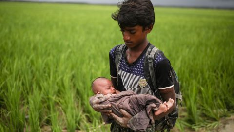A Rohingya child holds a baby on September 12, as refugees wade through the Naf River in Bangladesh.