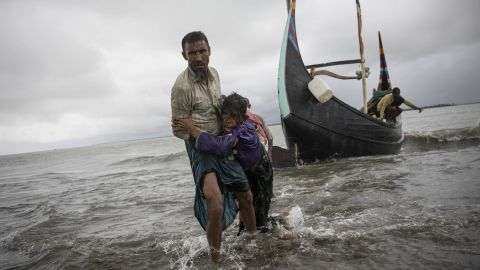 The woman is carried to shore after her boat crashed in Dakhinpara.