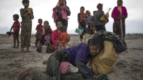 A woman collapses on September 12, after the wooden boat she and other refugees were traveling in crashed into the shore in Dakhinpara, Bangladesh.
