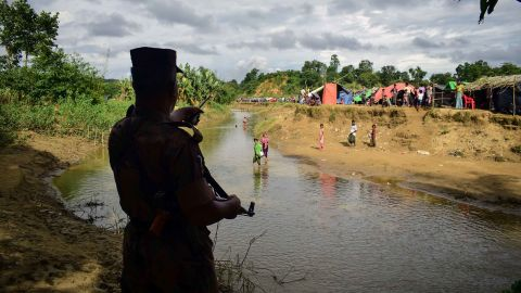 A Bangladeshi border guard orders Rohingya refugees to return to the Myanmar side of a small canal on August 29. Bangladesh has been struggling to cope with the influx of refugees.