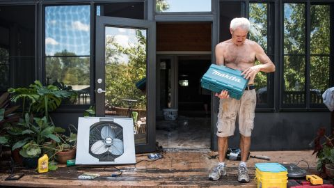 James Wade checks for water-damaged items as floodwaters recede in Middleburg on September 13.