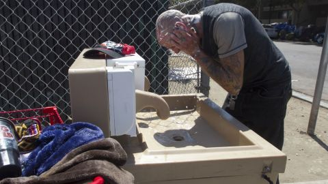 In this Sept. 5, 2017, photo, Jaime Lynn Hines washes his hands and face at one of the hand washing stations installed by the county in an attempt to stop the spread of Hepatitis A in San Diego. San Diego County officials earlier this month declared a public health emergency because of the spread of the liver disease that has killed 15 people and hospitalized 300 more.  (John Gibbins/The San Diego Union-Tribune via AP)