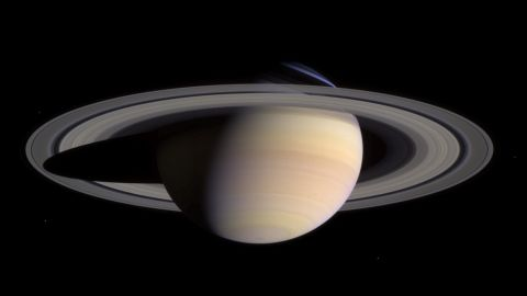 Saturn's pale colors and its rings come into view as Cassini approaches on May 7, 2004. This composite was made from images taken when Cassini was about 18 million miles (29 million kilometers) from Saturn. It also shows some of Saturn's moons.
