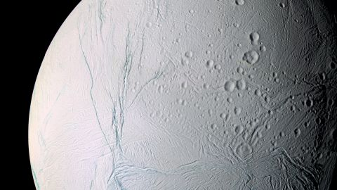 """Saturn's moon, Enceladus, is a small, icy world. For scientists, it's also one of the most interesting places in our solar system. Cassini discovered Enceladus is an active moon with a global ocean of liquid salty water beneath its crust. Planetary scientists now think Enceladus may possibly be hospitable to life.  """"Enceladus discoveries have changed the direction of planetary science,"""" said Cassini project scientist Linda Spilker. This mosaic was created from 21 false-color images taken during Cassini's close approaches to Enceladus on March 9 and July 14, 2005."""
