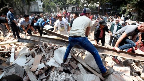 People remove debris off a building that collapsed in Mexico City.