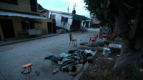 People sleep on the street next to damaged homes in Jojutla on September 20.