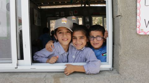 Nine-year-old Sundus Zawahra, left, and eight-year-old Nagham Ali, right, peer through the window of their fourth grade class with a friend at the school.
