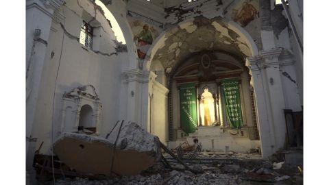 Chunks of fallen masonry lie by an altar in Santiago the Apostle Catholic Church.