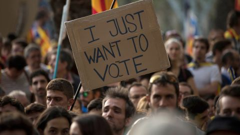 """A banner reading """"I just want to vote"""" is seen as demonstrators gather outside the Catalan high court."""