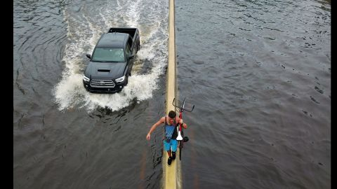 A man walks on a highway divider while carrying his bicycle through San Juan, Puerto Rico, on Thursday, September 21.