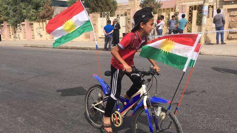A boy rides a bike outside of polling station.