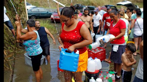 People collect water from a natural spring created by landslides in Corozal, Puerto Rico, on Sunday, September 24. Puerto Rican Gov. Ricardo Rosselló said the island faces a humanitarian crisis.