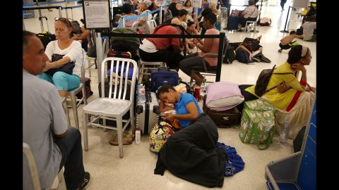 Yancy Leon rests at the Luis Muñoz Marin International Airport near San Juan on September 25. She's been waiting in line for two days to get a flight out.