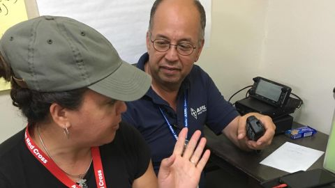 Oscar Resto works with another volunteer to pass along information at the Red Cross headquarters in San Juan, Puerto Rico.