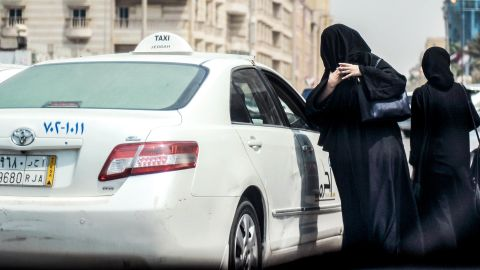 A Saudi woman prepares to get into a taxi on a main street in the Saudi coastal city of Jeddah on September 27, 2017.