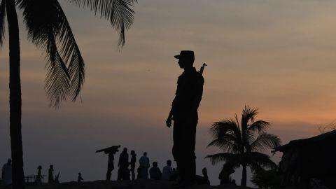 A Bangladeshi border guard keeps watch September 16 near the beach of Sharapuri Dwip, where many Rohingya refugees land after crossing from Myanmar.
