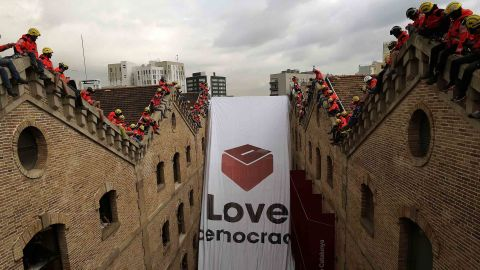 """Catalan firefighters unfold a banner with a ballot box and the words """"Love democracy"""" at the Museum of History of Catalonia in Barcelona on Thursday."""