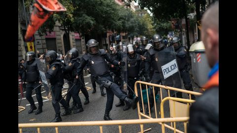 Spanish riot police remove fences thrown at them as they try to prevent people from voting in Barcelona, Spain, on Sunday, October 1.