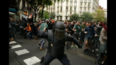 Spanish riot police swings a club against would-be voters near a school assigned to be a polling station by the Catalan government in Barcelona, Spain, Sunday, Oct. 1, 2017. Spanish riot police have forcefully removed a few hundred would-be voters from several polling stations in Barcelona. (AP Photo/Manu Fernandez)
