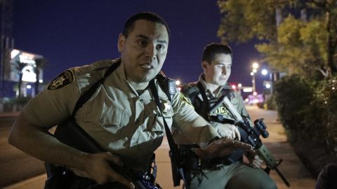 Police officers advise people to take cover in the wake of the shooting.