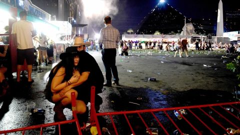 """A couple huddles after shots rang out at a country music festival on the Las Vegas Strip on Sunday, October 1, 2017. At least 58 people were killed and almost 500 were injured when <a href=""""http://www.cnn.com/2017/10/02/us/las-vegas-shooter/index.html"""" target=""""_blank"""">a gunman opened fire</a> on the crowd. Police said the gunman, 64-year-old Stephen Paddock, fired from the Mandalay Bay hotel, several hundred feet southwest of the concert grounds. He was found dead in his hotel room, and authorities believe he killed himself and that he acted alone. It is the deadliest mass shooting in modern US history."""