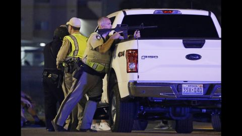 A police officer takes position behind a truck.