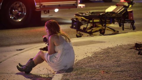 A woman sits on a curb at the scene of the shooting.