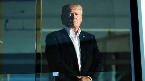 Trump, who is a keen golfer, watches the action from the clubhouse at Liberty National Golf Club.