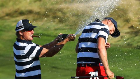 Berger is sprayed with champagne by a cigar-toting Hoffman.