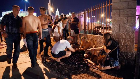 People gather around a victim outside the festival grounds.