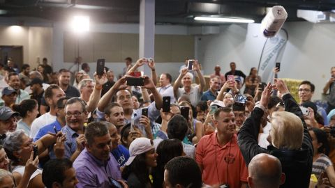 President Donald Trump tosses paper towels into a crowd as he hands out supplies at Calvary Chapel on October 3, 2017, in Guaynabo, Puerto Rico.