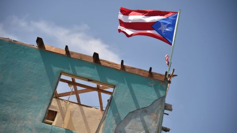 A flag of Puerto Rico is seen on a damaged house in Yabucoa, in the east of Puerto Rico, on September 28, 2017. The US island territory, working without electricity, is struggling to dig out and clean up from its disastrous brush with hurricane Maria, blamed for at least 33 deaths across the Caribbean. / AFP PHOTO / HECTOR RETAMAL        (Photo credit should read HECTOR RETAMAL/AFP/Getty Images)